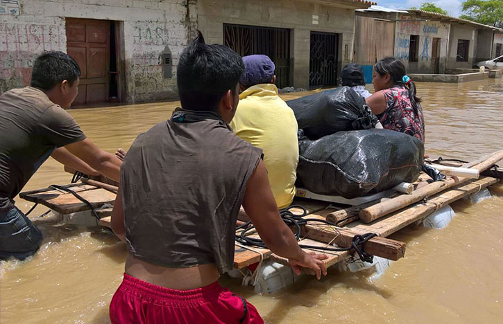 Men help push a raft through flooded streets