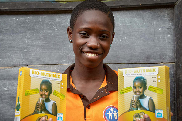 A student in Togo holds 2 boxes of nutrition supplements made from mushrooms