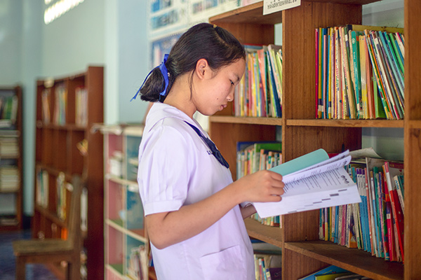 A student in Thailand reading books in the library