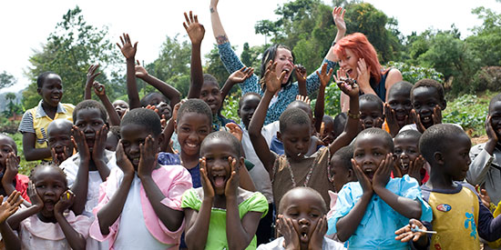 A group of Ugandan children make faces and wave their arms in the air.