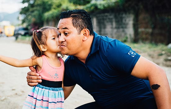 A little girl gives a man a kiss on the cheek