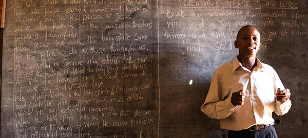 a teacher standing in front of a chalkboard