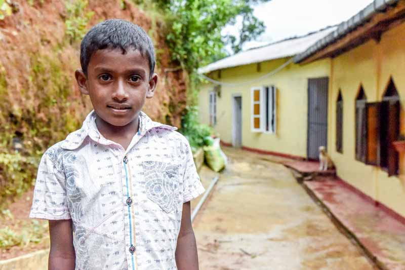 A boy standing outside his home