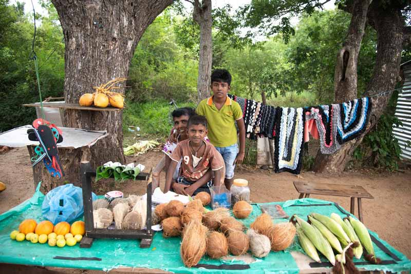 A family sits on ground while selling their produce