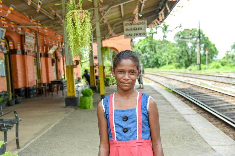 A girl stands outside the trainstation