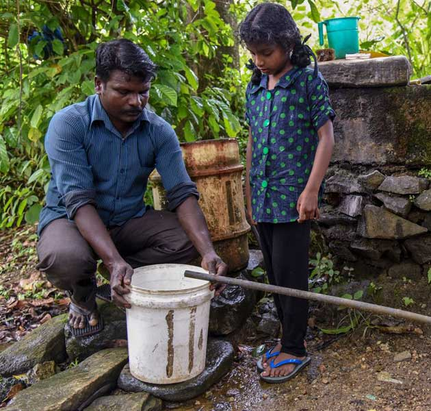 A father and his daughter collecting water in a bucket