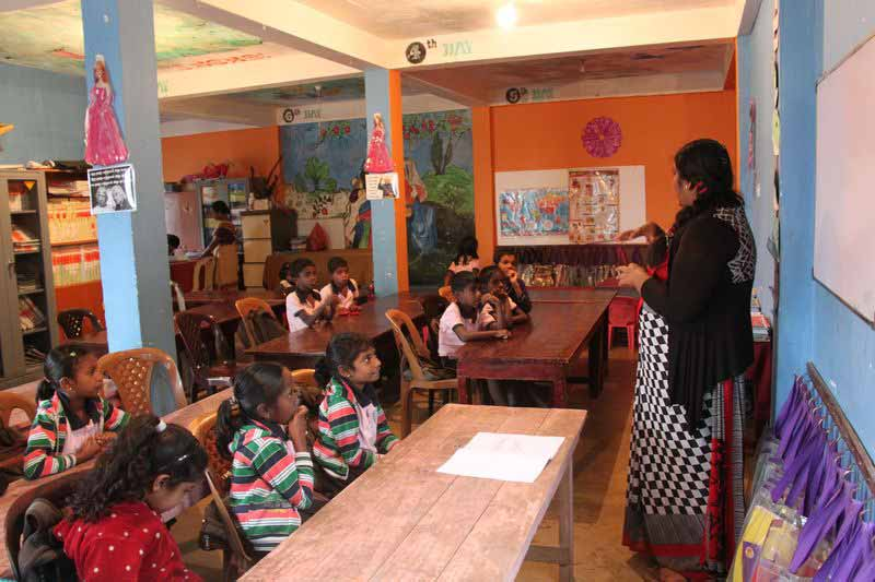 A teacher standing in front of students in classroom