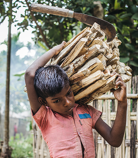 Sujit is seen here carrying a large bundle of wood on his shoulder.