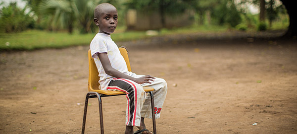 A boy sitting outside in a chair