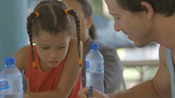 Mike Donehey (Lead Vocal) coloring with his sponsored Child in the Dominican Republic.