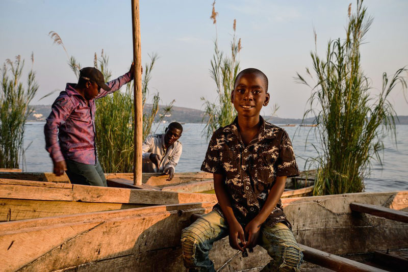 A boy sits near water next to a boat