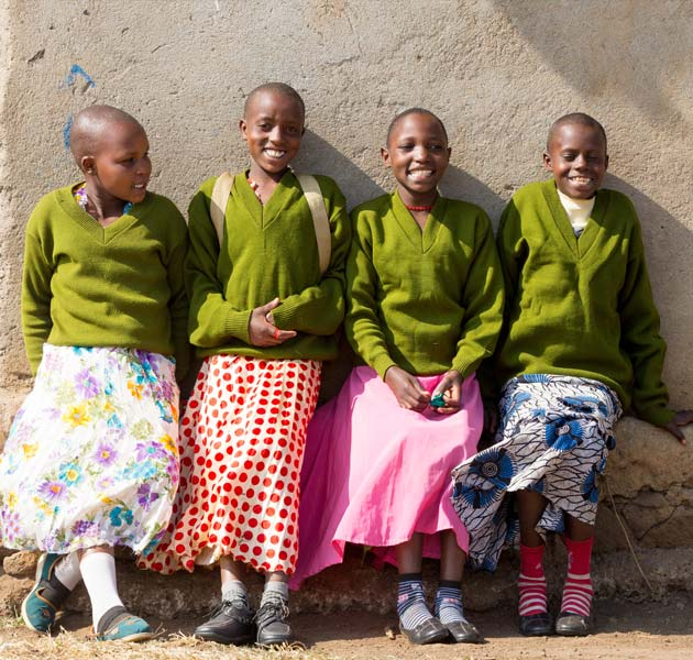 Four Tanzanian girls standing together wearing green uniform sweaters