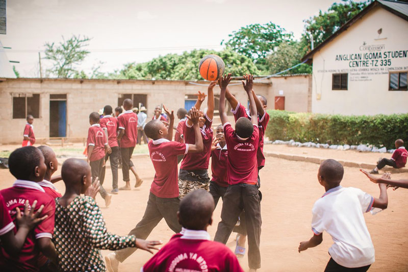 A group of students play basketball