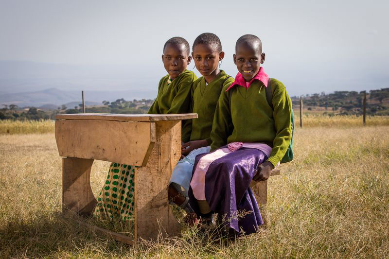 Three students sit at a desk outside