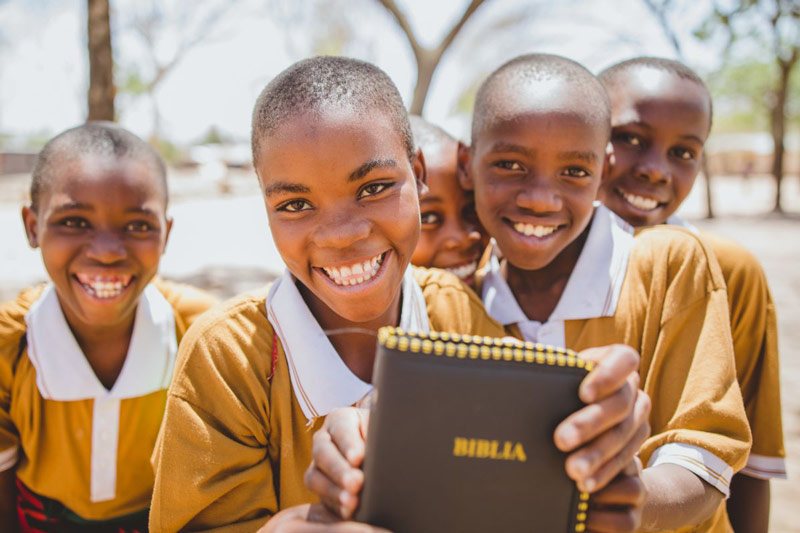 Kids smile holding up a Bible