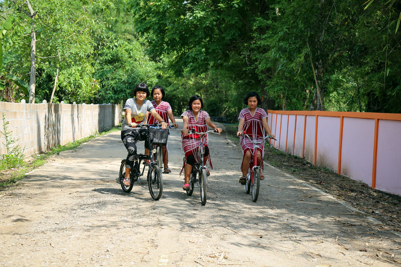 A group of girls ride bicycles