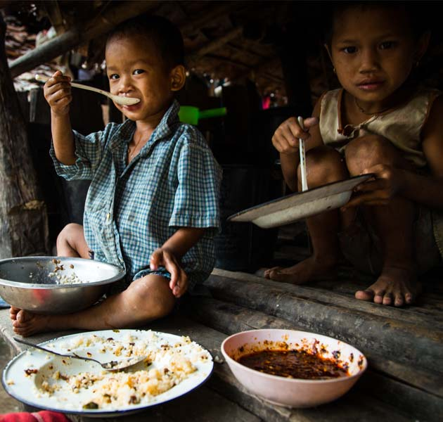 Young children sitting in their home eating a meal