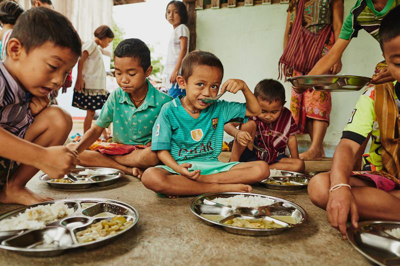 A group of children eat a meal at their child development center