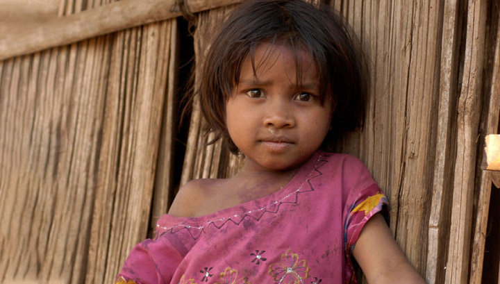 A young girl standing in front of her home in India