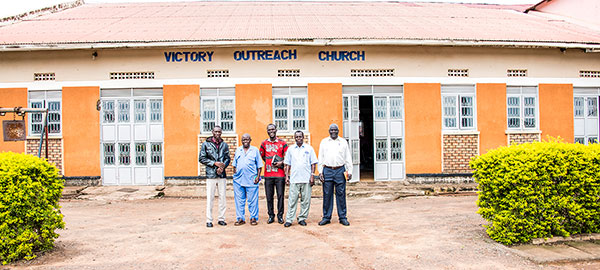 A group of people standing in front of a church in Uganda