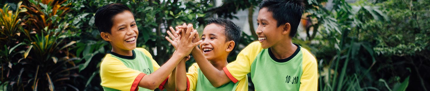 Three boys laughing and clasping hands