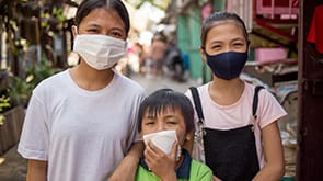 Three children with masks over their mouths and noses