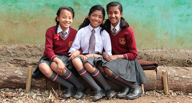 Three girls sitting on bench outside wearing school uniforms