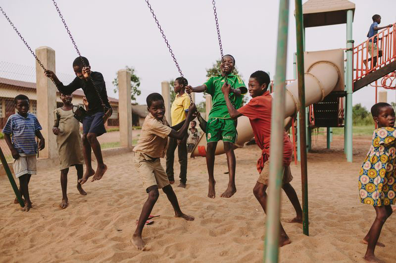 A group of children play joyfully on a playground