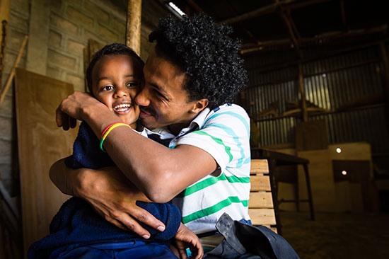 An Ethiopian man hugs and squeezes and young boy