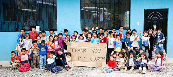 A group of children in front of a blue building hold a cardboard sign with a thank you message written on it