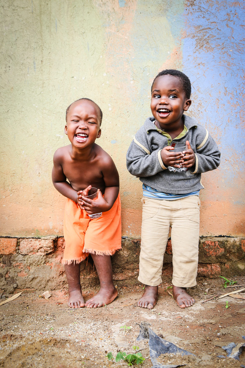Two young boys stand against a wall as they play and laugh