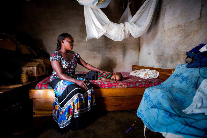 A mother sits with her child on their bed under a mosquito net