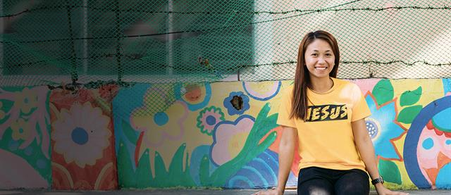 "A young woman sits on a floral painted wall and smiles with a yellow ""Jesus"" shirt on"