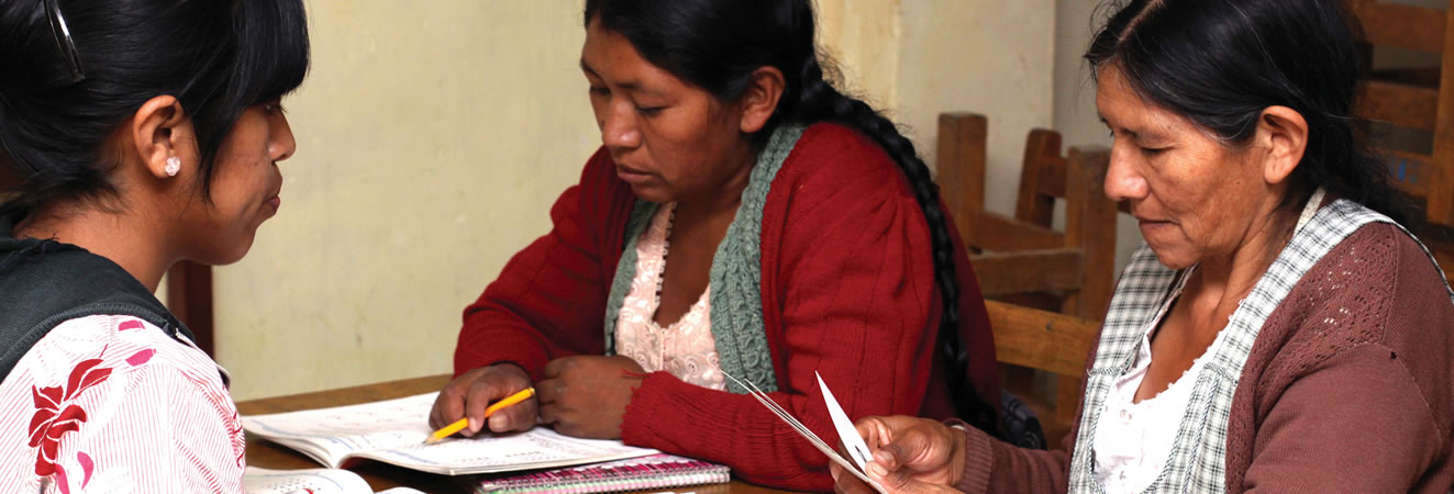 A tutor in Bolivia helping mothers with literacy