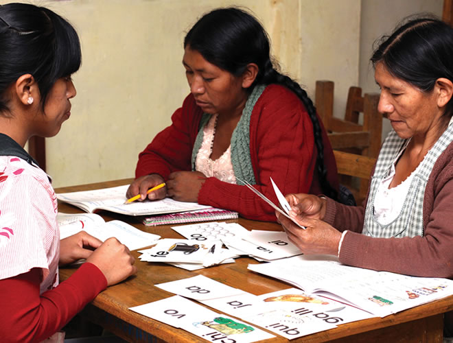 A tutor gives literacy lessons to two mothers