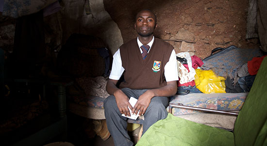A Kenyan teenager sits on his couch/bed in his home in the Mathare Valley slum of Nairobi