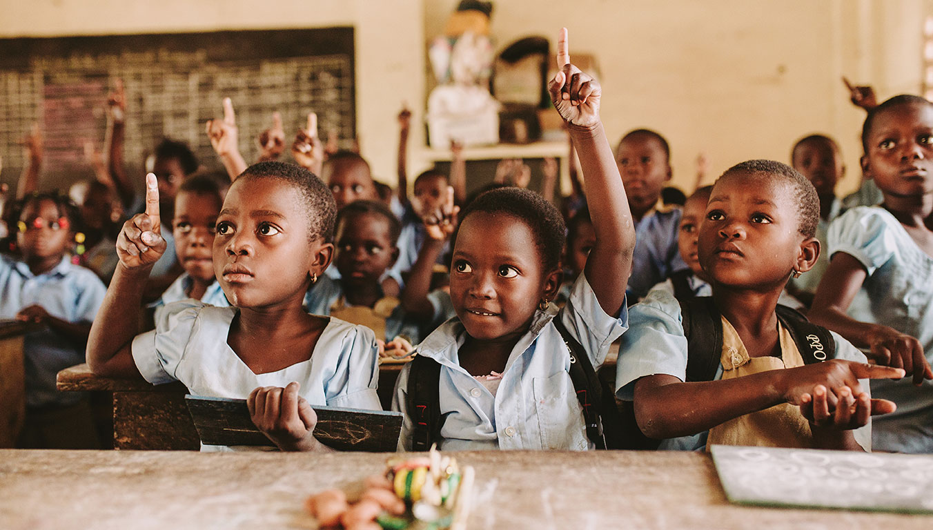 Aklobessi raising her arm in school at a Compassion center