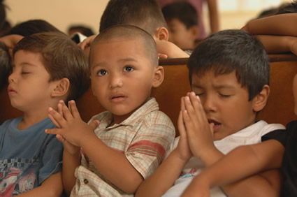 three young children praying