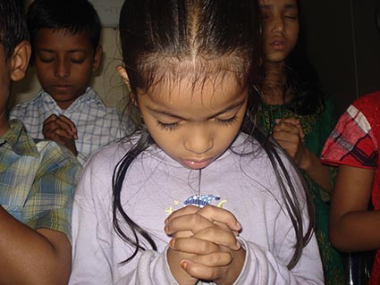 a girl bows her head in prayer