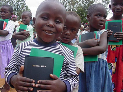 a line of children holding bibles