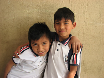 two boys standing together with their arms on each other's shoulders