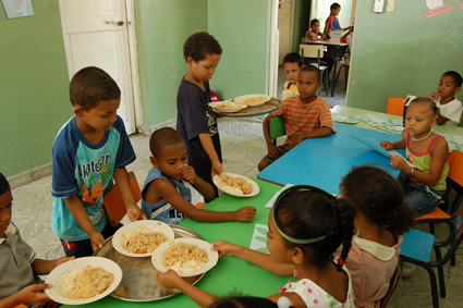 young children serving food to other children