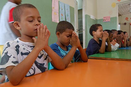 several children at a table are praying