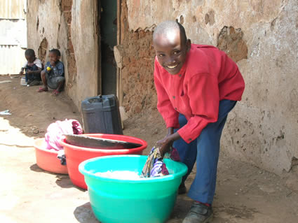 a boy washes clothes in a bucket