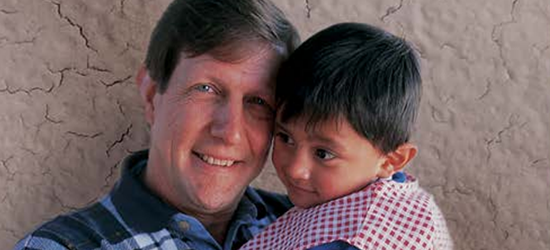 Wess Stafford holding a child