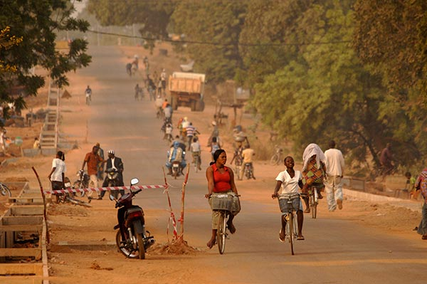 A road in Burkina Faso with many people riding bikes
