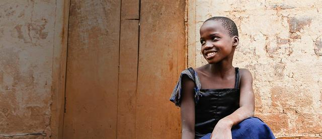 A smiling young girl in a black and blue dress
