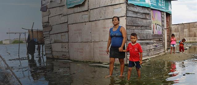 A woman and boy hold hands as they walk through ankle-deep water outside their home