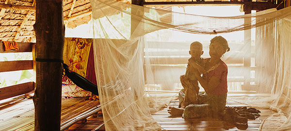 A mother and baby underneath a malaria mosquito bed net