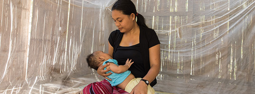 A mother holds a baby while sitting on a bed underneath a malaria bed net